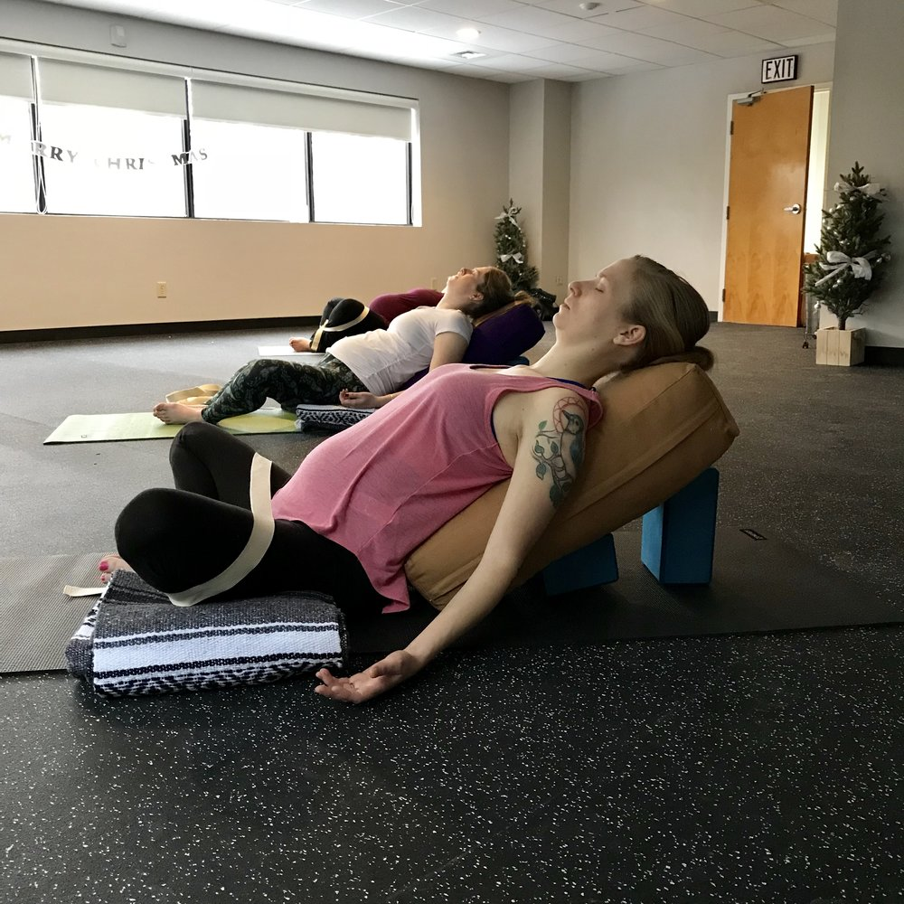 A group of Daniella's prenatal yoga students sink into a supported variation of supta baddha konasana (reclined bound angle pose) for final relaxation.