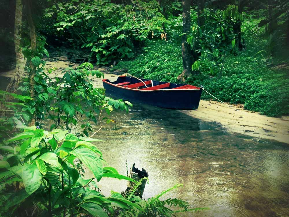 A boat sits tied up on the edge of a small river near Votua village.
