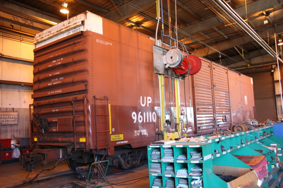 A Union Pacific boxcar gets running repairs at the Avon car shop