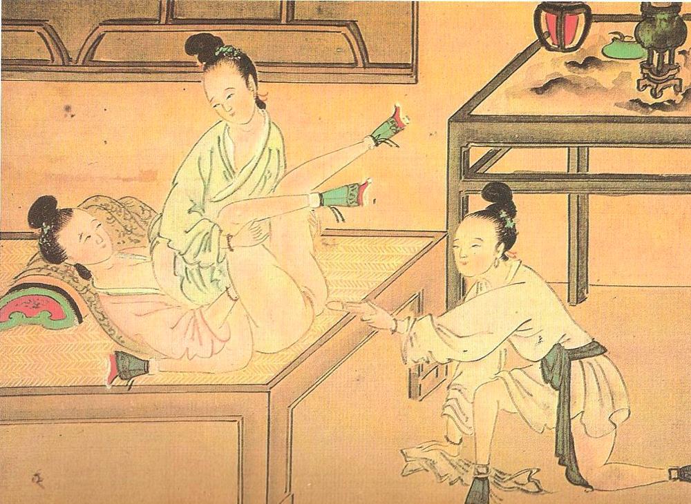 Three women using a dildo.