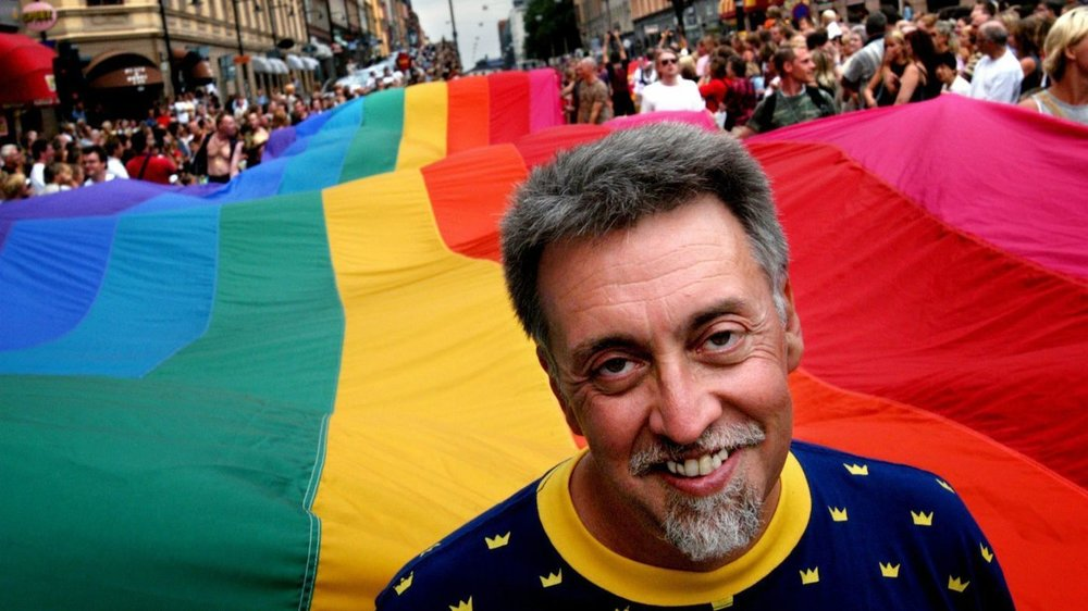 Gilbert Baker in front of his mile long flag for Stonewall 25 in 1994 (© Fredrick Persson EP)