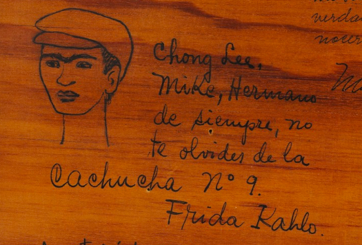 "Close up of frida's note to Miguel n. lira: ""hermano de siempre no te olvides de la cahucha no 9, Frida Kahlo""— ""Forever brother, do not forget la Cachucha no. 9, Frida Kahlo."" Alongside it is her doodle of herself wearing the cap for which the group was named, 1948."
