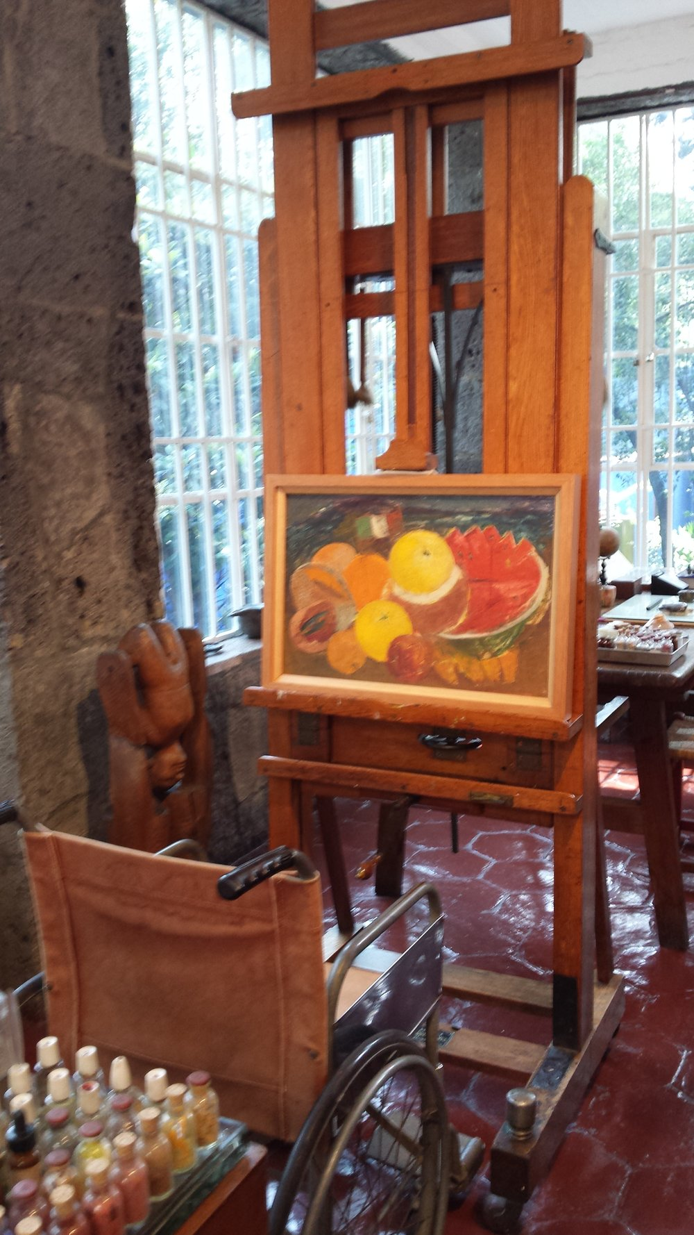Frida's studio with her wheelchair and adjustable easel, on display at La Casa Azul museum in Mexico.