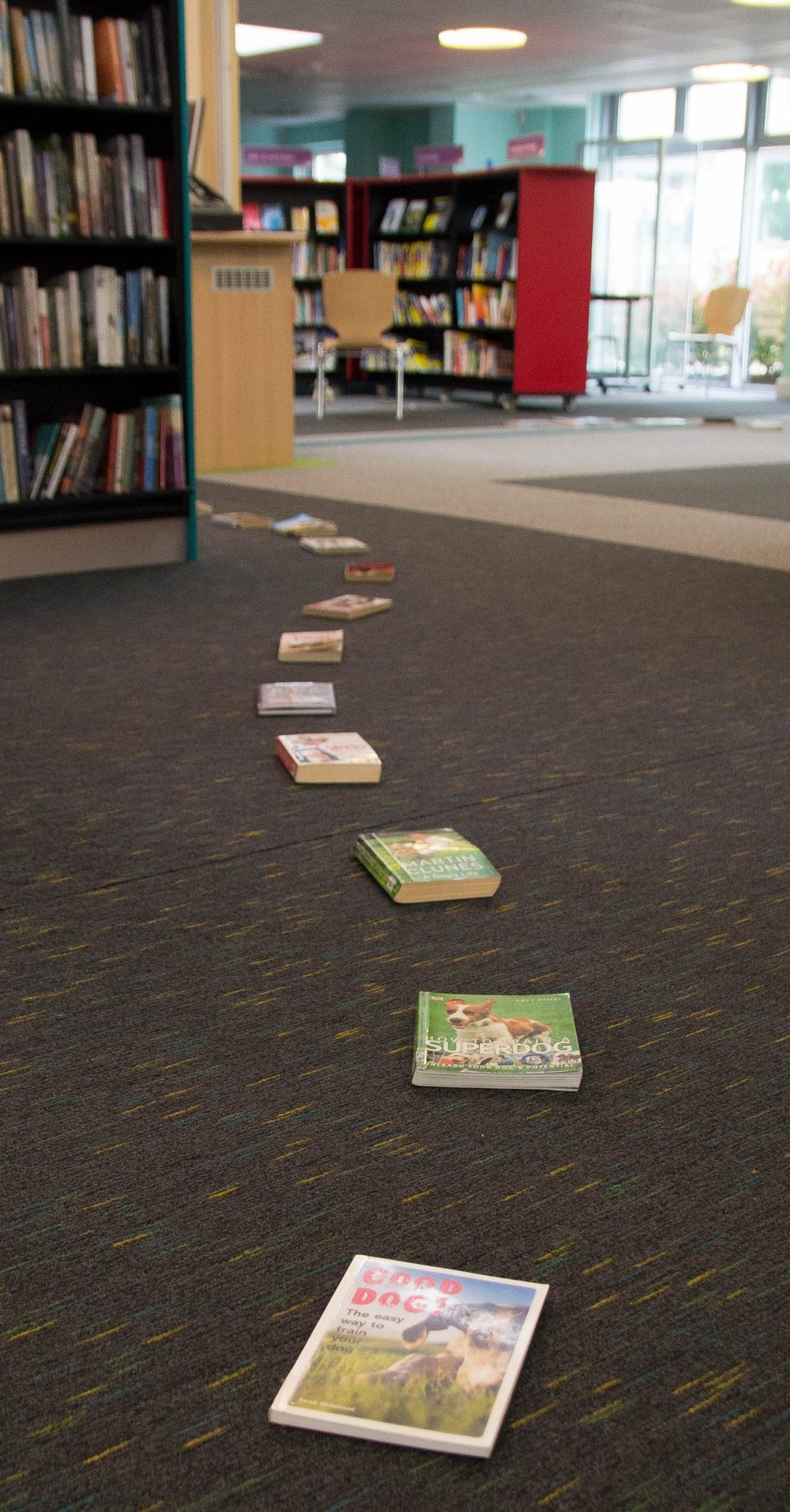 A trail of books leads the audience into the depths of the library