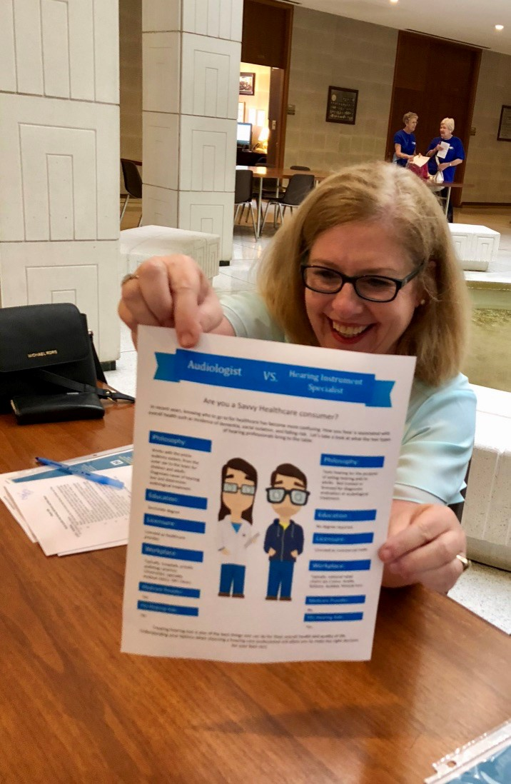 Dr. Sheri Mello displays a handout created by Dr. Melissa Karp explaining the difference between Audiologists and Hearing Aid Dispensers.