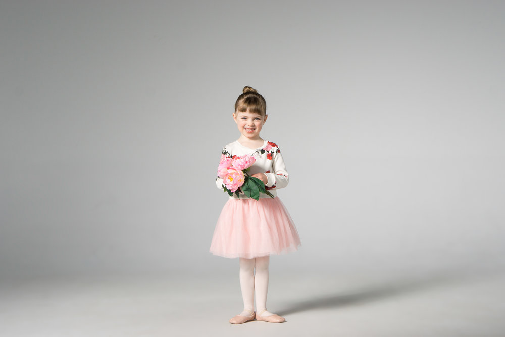 cute ballet dancer holding pink flowers