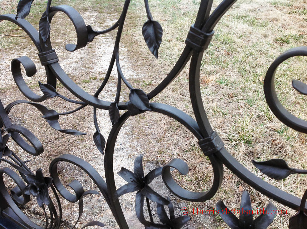 Hand forged scrolls with traditional hot formed collars wrap and connect the elements together. Here the lilies, daffodils, and leaves can be seen