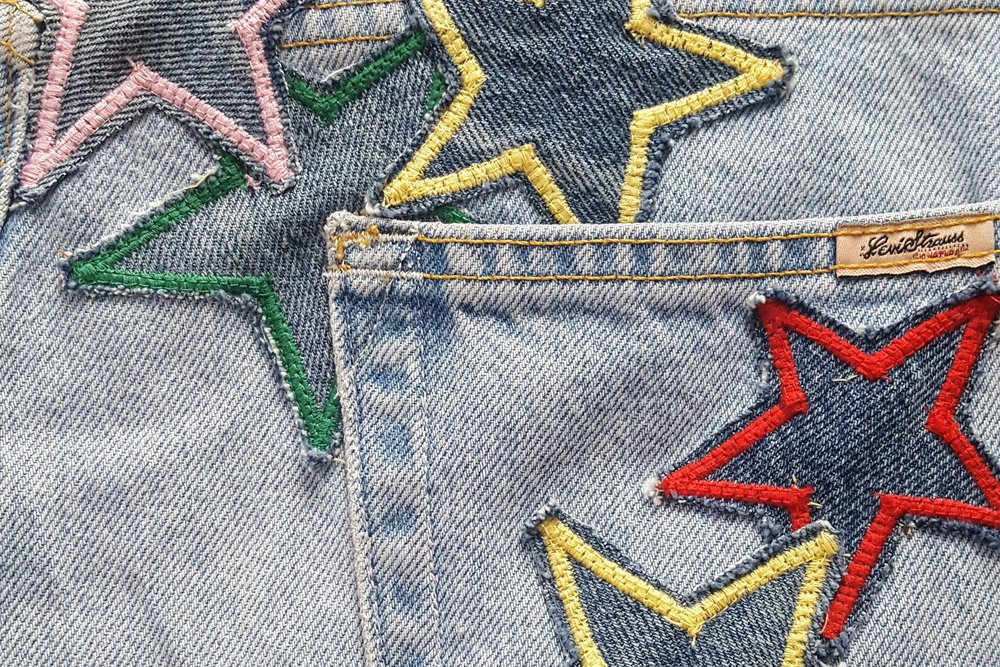 Star patches stitched on jeans.  The green star is reenforcing a hole developing near the pocket.