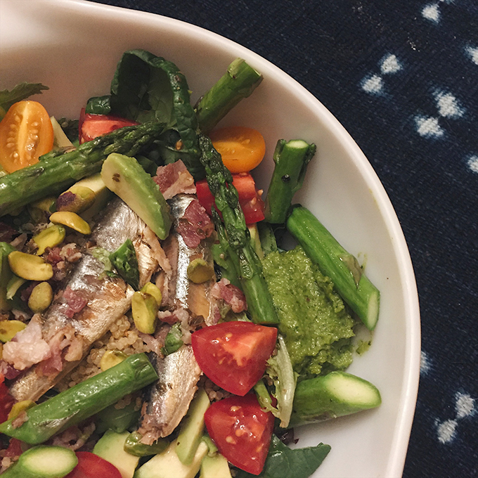 Nutrient-dense random veg bowl: garlic scape pesto, organic asparagus, avocado, bacon bits, tomatoes, raw pistachios, marinated onions, sardines and CSA greens.