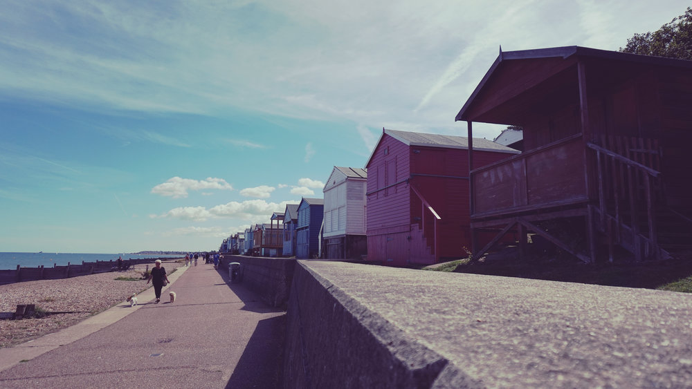 a stretch of seaside with beach huts