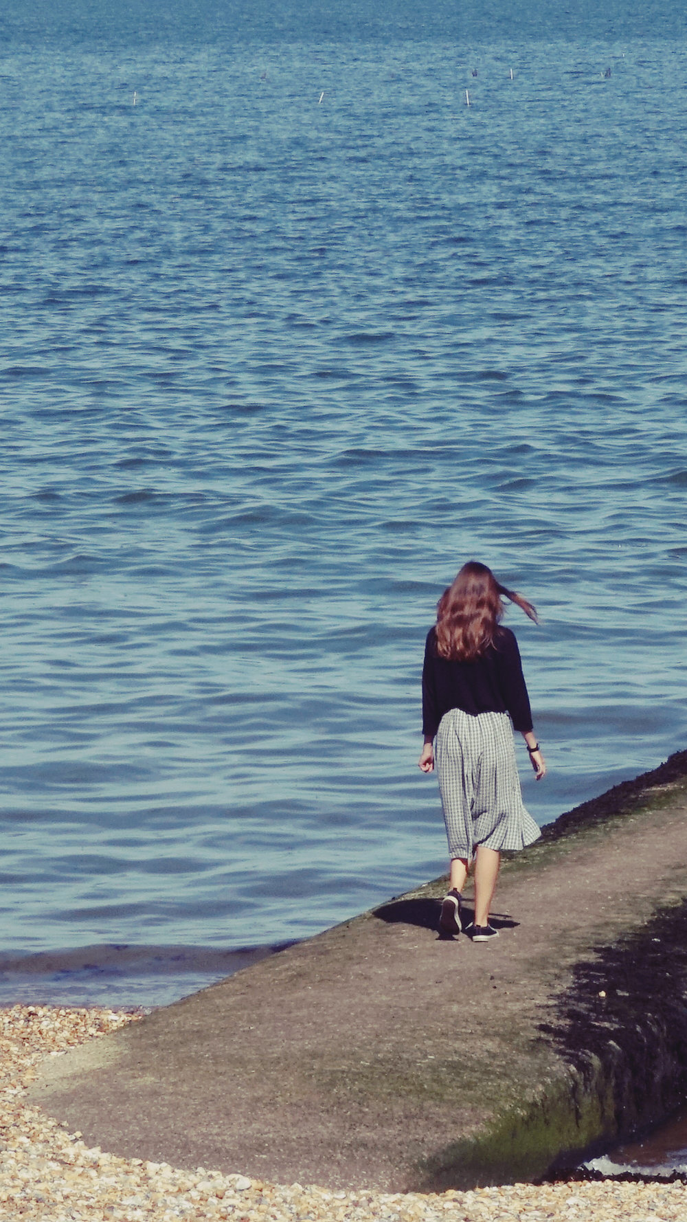 a girl walking towards the sea