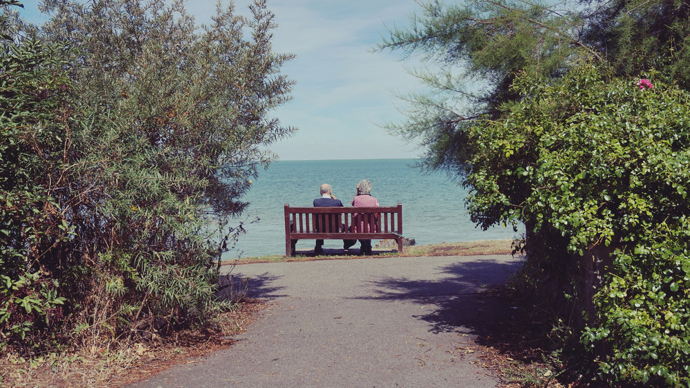 an elderly couple looking out at the sea