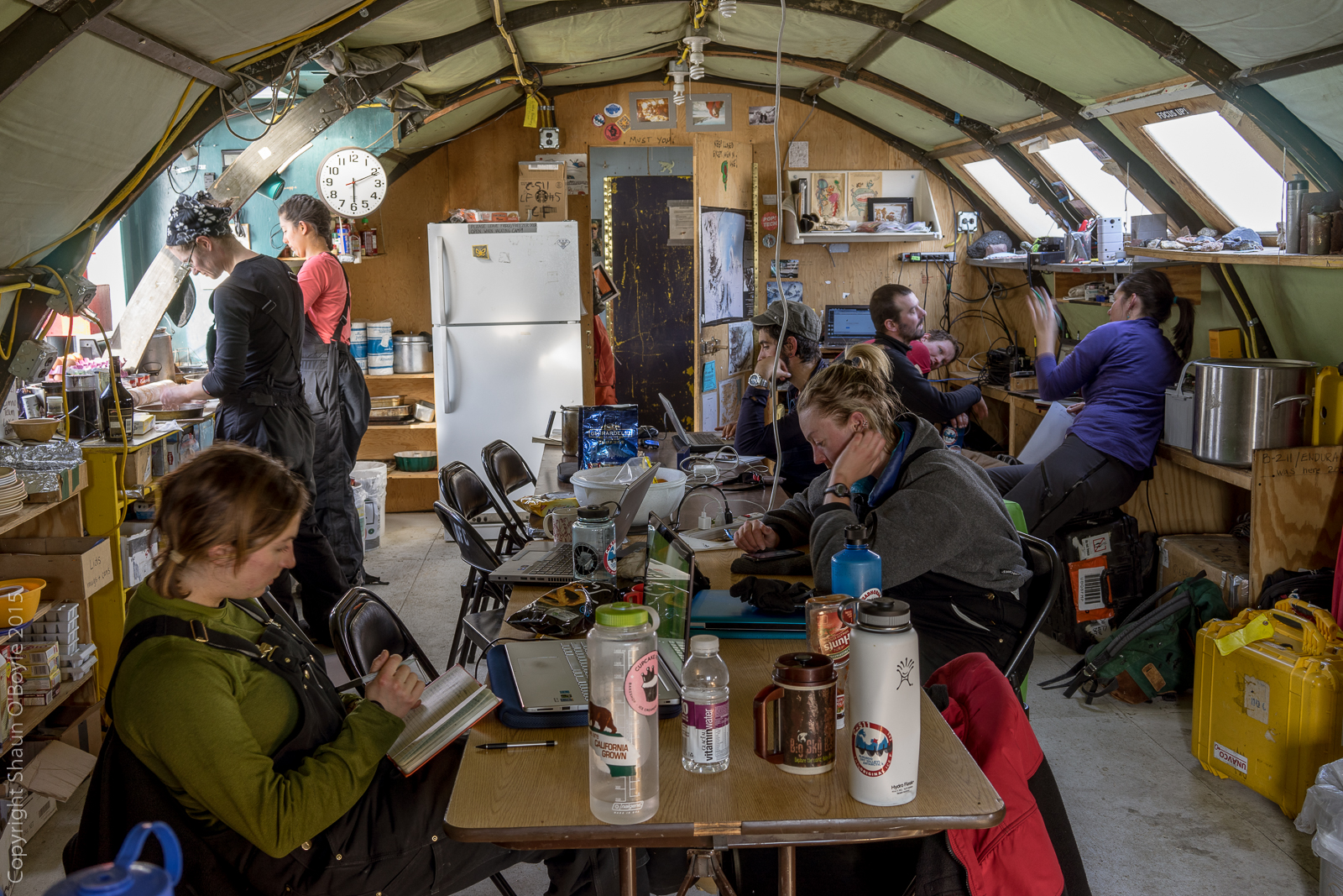 A crowded Jamesway building, used for cooking, dining, work and social space. Scientists and graduate students are working here on the LTER (long term ecological research) project.