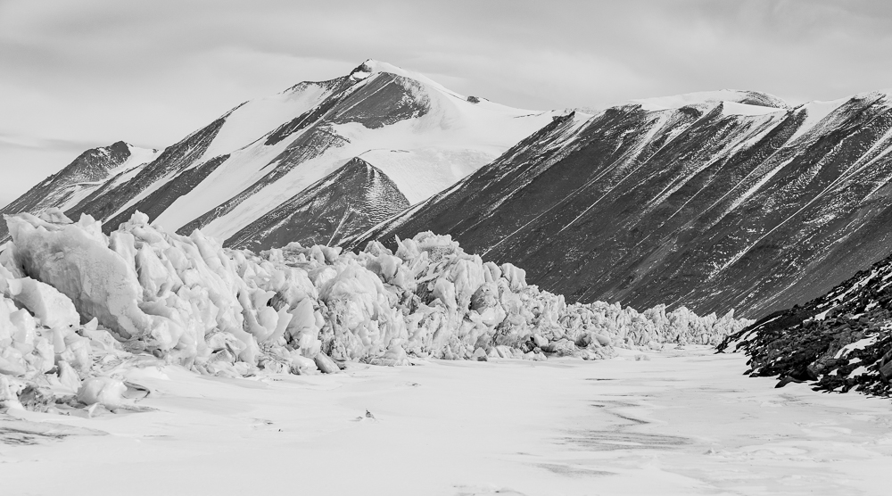 """Pressure ridges formed by hte sea ice and glacier pressure pushing the ice onto the shore, we we able to drive the snowmobiles between the pressure ridges and the mountain slopes on the """"Moat""""."""