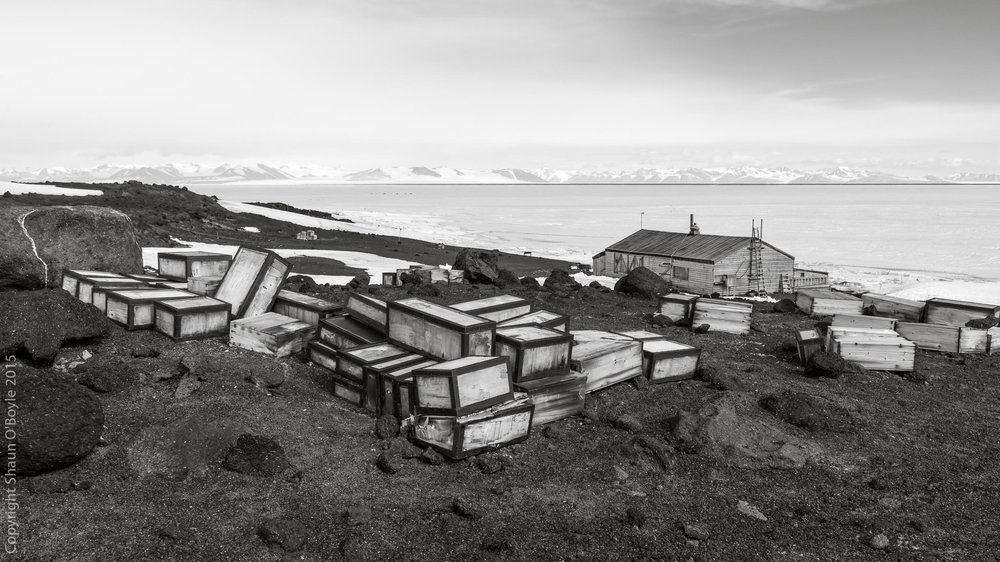 Stores on the ramp above the hut. Royal Society Range on distant shore of McMurdo Sound. The thin black line is open ocean approaching Cape Evans as the seasonal ice begins to break up.