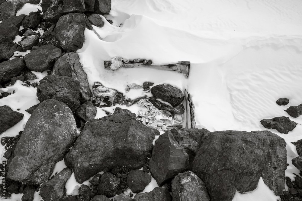 Crate full of items in the remains of the igloo which include canvas, wool, penguin skins and rocks.