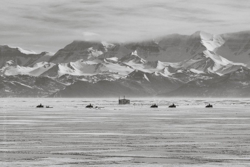 Snow mobiles on McMurdo Sound from Hut Point. Probably the biology team returning from Big Razorback Island where they have a Weddell Seal study area. #3 Fish Hut in background.