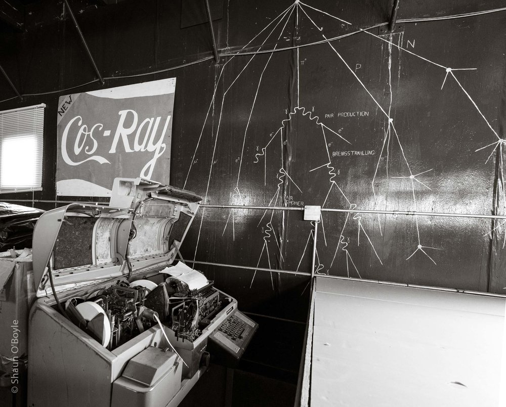 Wall mural of cosmic rays, and the old teletype machine used for recording/transmitting data.