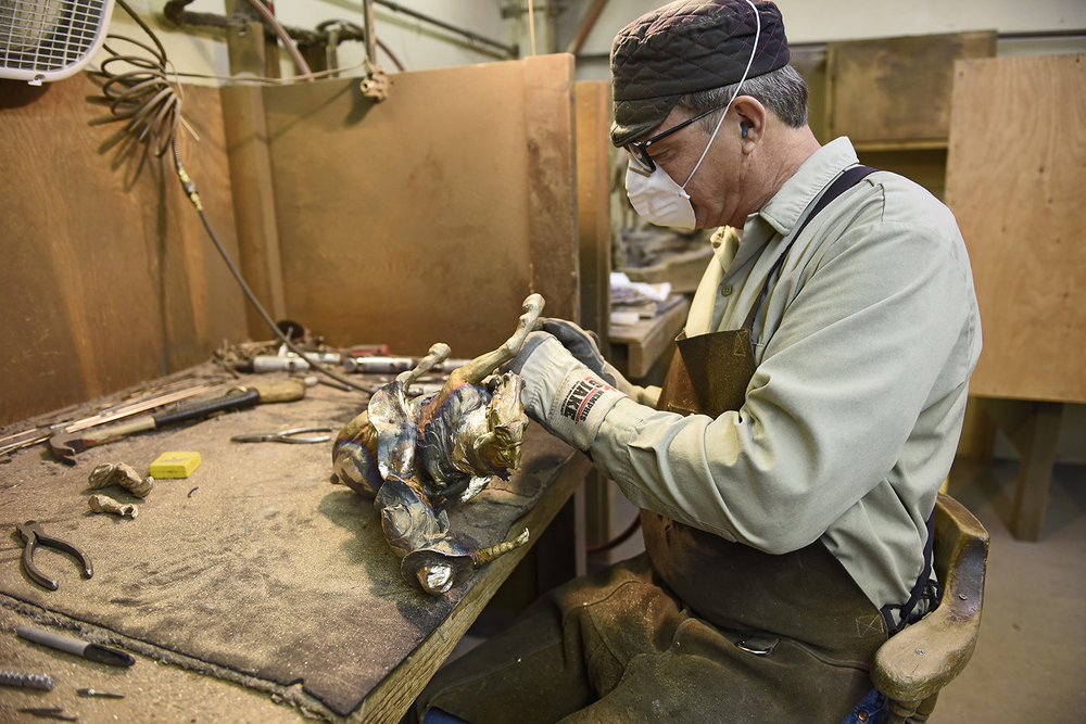 "In the details: - The raw bronze cast, once released from the ceramic investment, still has the sprues attached (now bronze) which will need to be cut off and the surface smoothed. Here's ""Big Mike"" in the metal shop welding and adding fine details like ropes and reins."