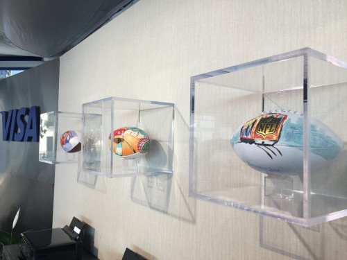 The three different designs displayed in the VISA VIP area above Super Bowl City.