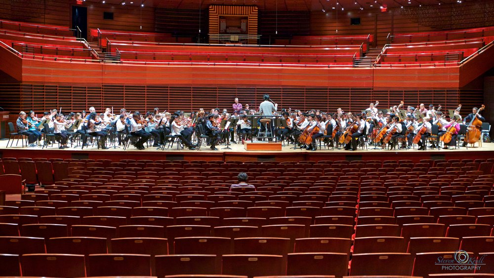 PMAY orchestra students rehearse onstage with Lio Kuokman, assistant conductor of The Philadelphia Orchestra, in the Kimmel Center's Verzon Hall during their 2015 Festival.