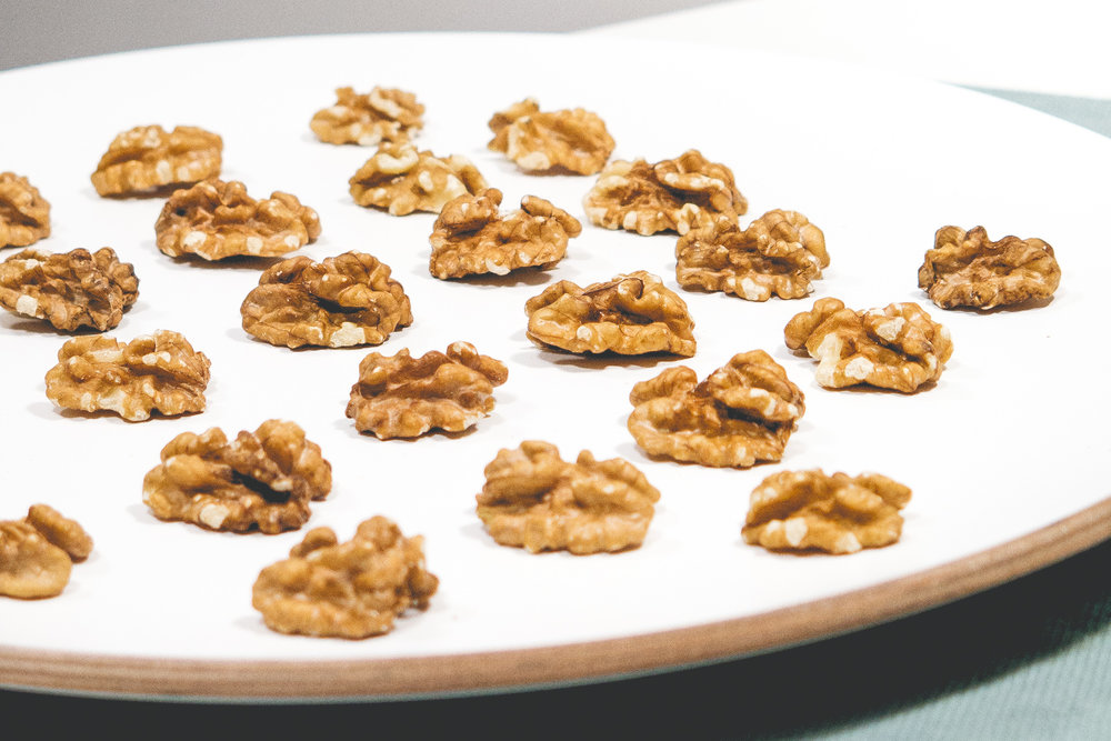 Walnuts arranged in a grid on a white dish