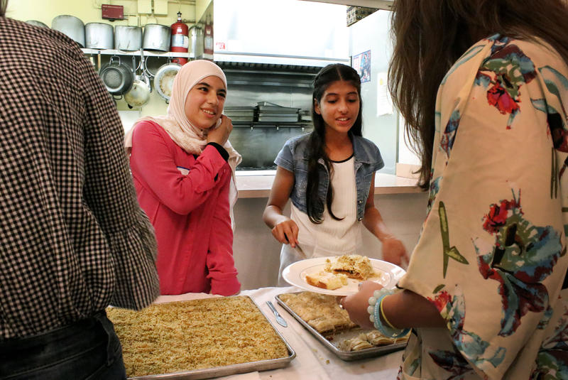 Two Syrian children serve desserts like baklava to guests at A Taste of Syria dinner co-hosted by O, Miami and RAA.
