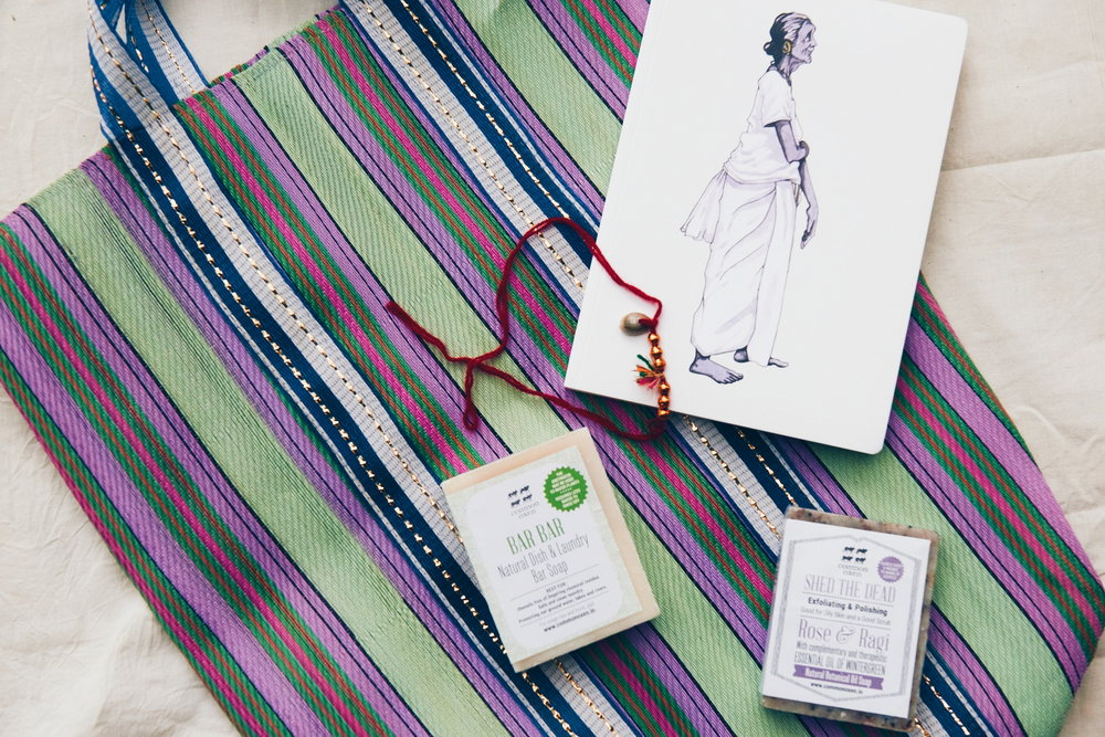 An Indian tote, soaps, Kalonji seeds, a notebook, Rakhi bracelet, and recipes