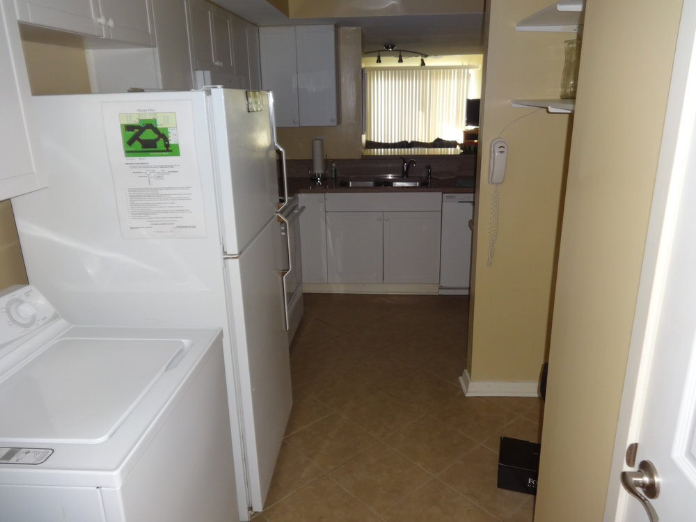KITCHEN WITH WALK-IN PANTRY AND ADJACENT WASHER / DRYER.