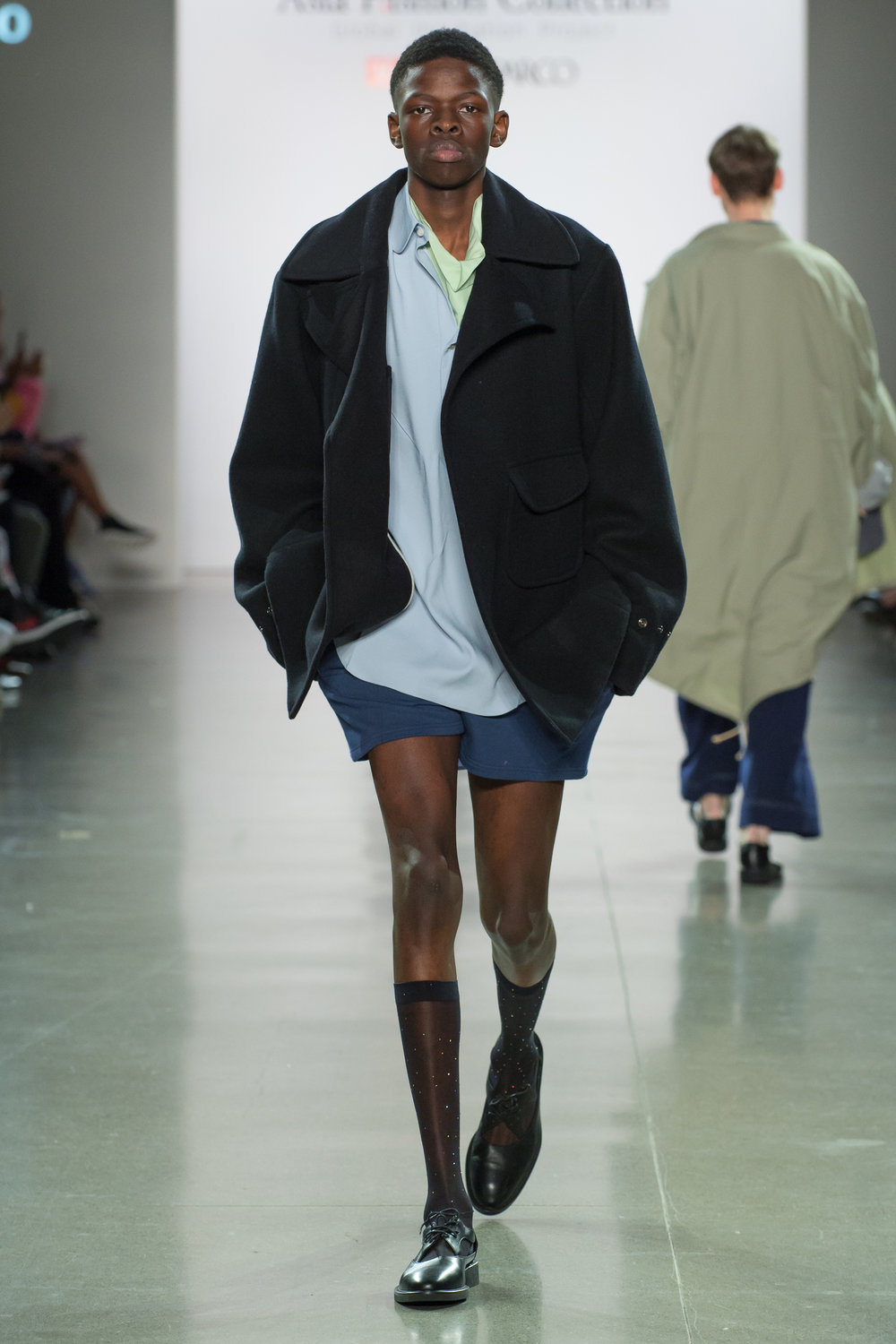 Look 5  -Oversized pea coat in black cashmere blend melton  -Big polo in sky blue double face heavy georgette  -Fold collar top in apple green silk satin  -Short shorts in denim blue cotton terry  -Stocking in black with white crystals