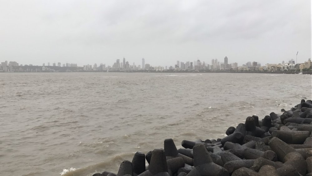 the view of mumbai city from the seawall along marine drive