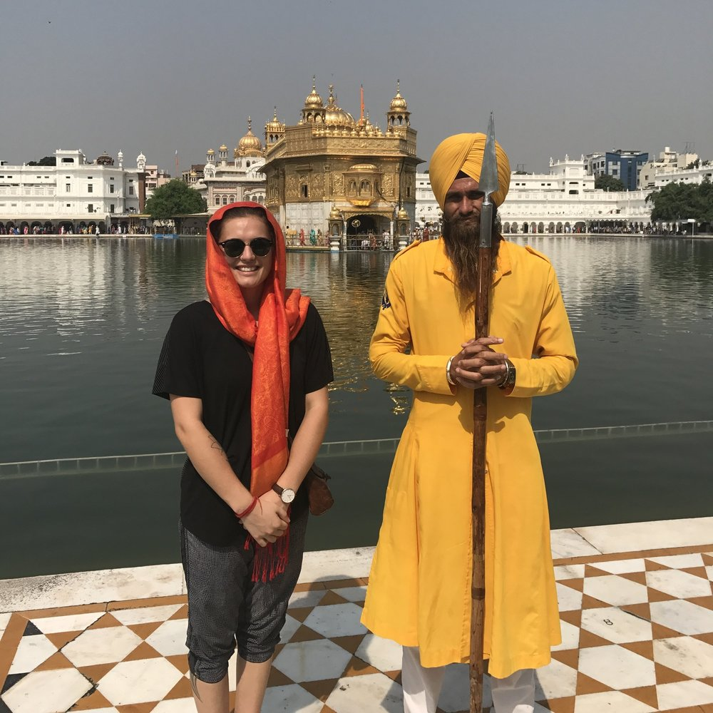 a photograph of me with a golden temple guard, with the temple in the background