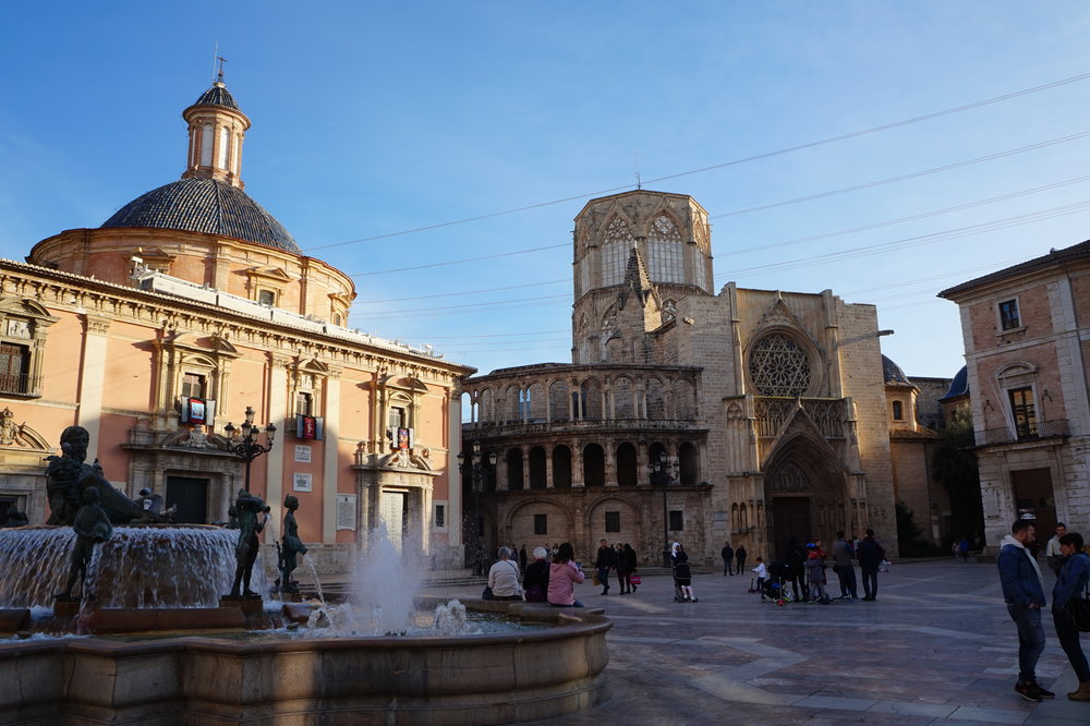 the rounded building in the background is the catedral de sevilla - a unesco world heritage site. you can see the laundry lines hanging above the cathedral square!