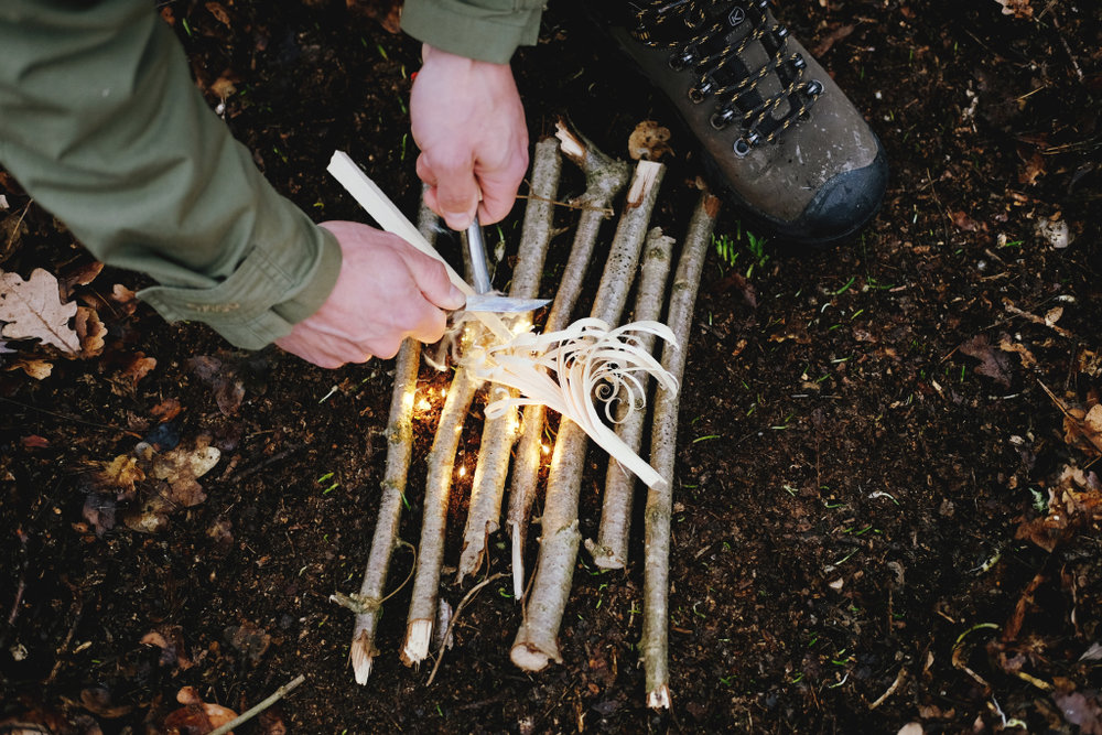 Lighting a fire with a fire steel and birch bark.