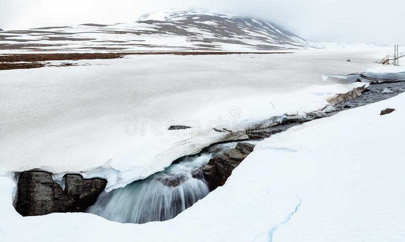 río-ártico-que-cae-en-un-agujero-en-nieve-57217890.jpg