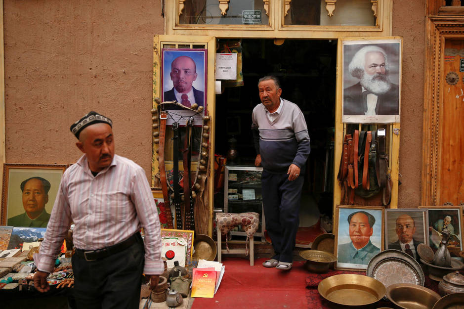 portraits-of-china-s-late-chairman-mao-zedong-soviet-state-founder-vladimir-lenin-and-german-philosopher-karl-marx-are-displayed-outside-an-antique-shop-in-the-old-town-in-kashgar-xinjiang-uighur-autonomous-regio.jpg