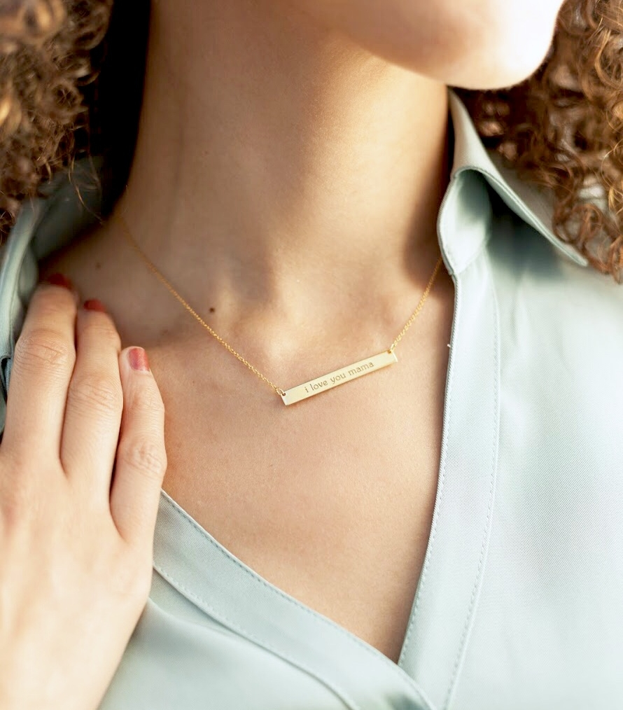 Close up shot of woman wearing Tiny Tags gold bar necklace