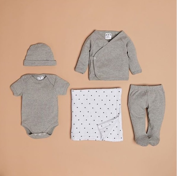 YKC baby hat, onsie, long sleeved t-shirt, footed pants in grey and a grey polkdot blanket