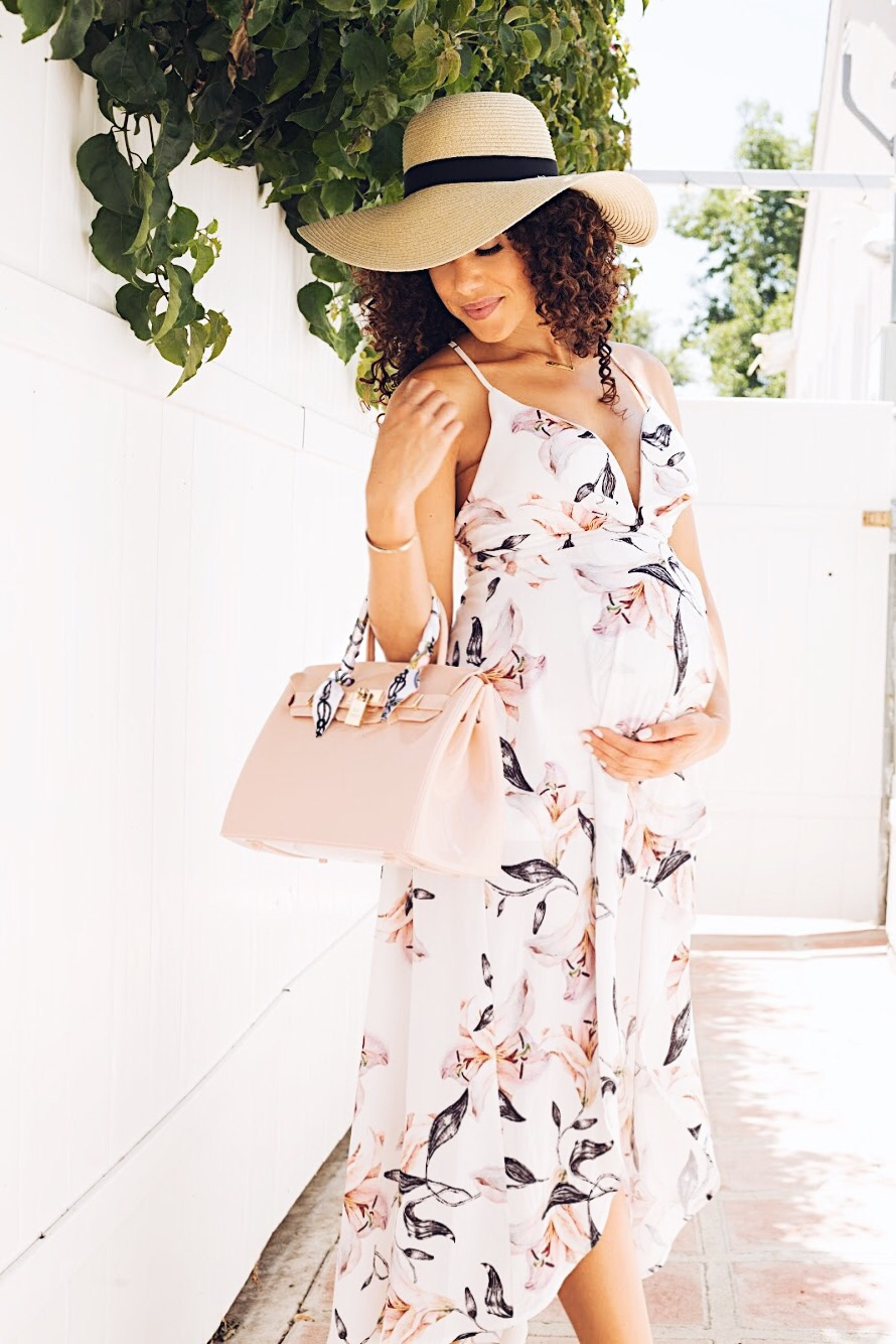 Pregnant woman posing in a floral dress and hat with her BIKI waterproof bag in NUDE color.