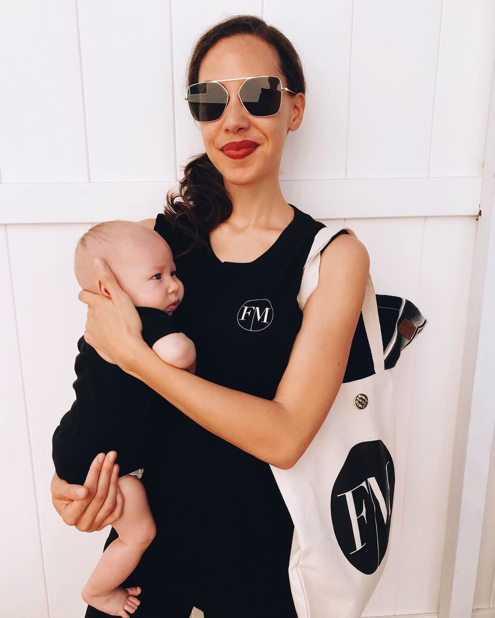 Woman wearing a black tank top with Fashion Mamas logo, black sunglasses and white bag with FM logo carrying a baby in a black cloth carrier