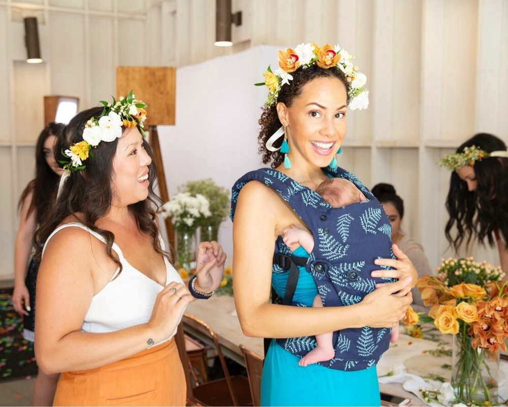 two darkhaired women wearing flower crowns at Baby Tula event