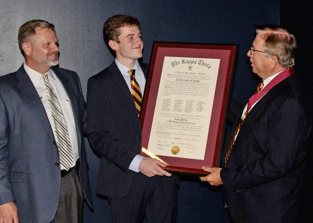 Fraternity President, Adrian Gonzalez (University of Texas Austin, '78) (right) presenting a Charter to the University of Iowa Chapter President, Colton Miller ('20), alongside National President-Elect Doug Dilling (Kansas State University, '84) (left).