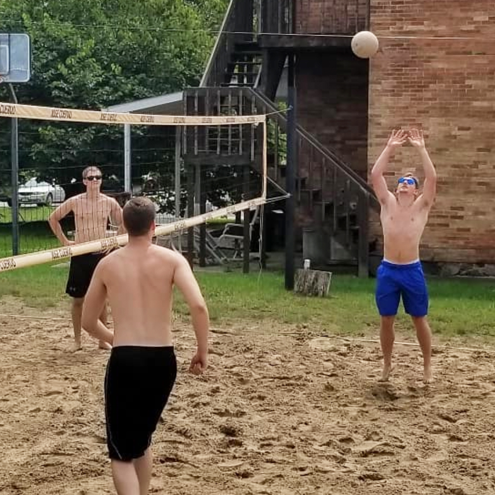 Brother Clark (right) playing volleyball outside the old chapter house at Trine University.
