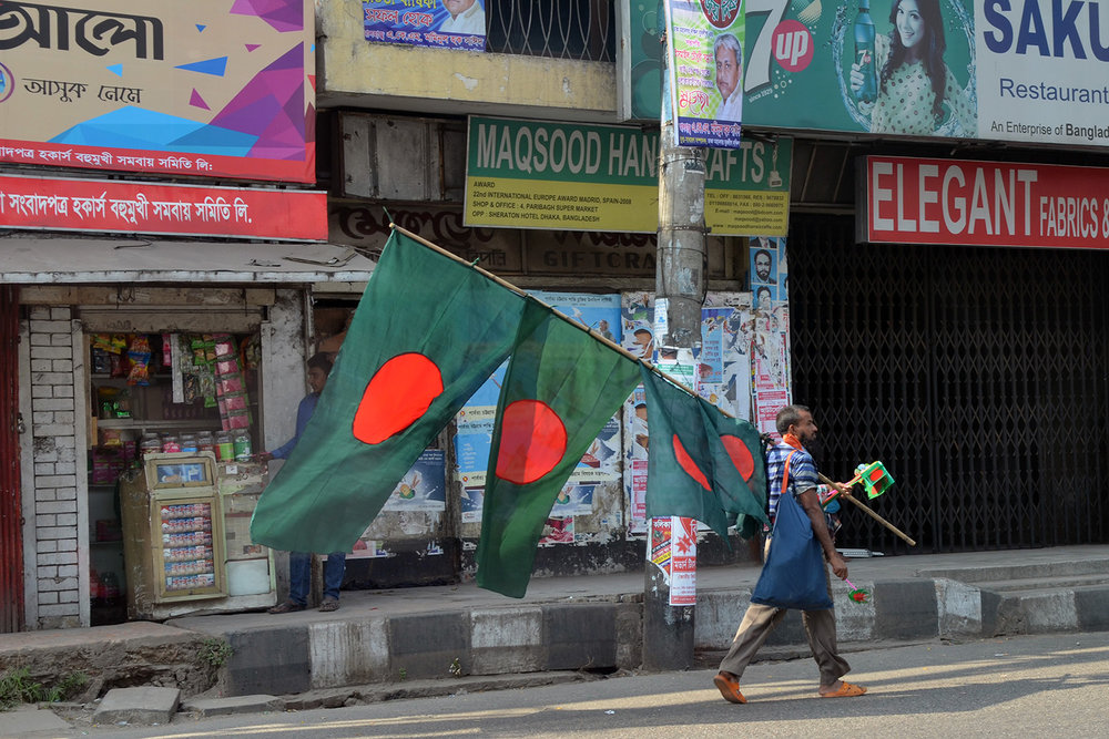 A man sells Bangladeshi flags ahead of Victory Day, celebrating the country's independence. Photo by Madeline Ewbank