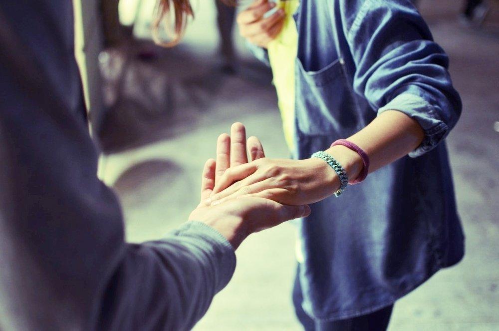 En person støtter sig til en anden person for at undgå at falde