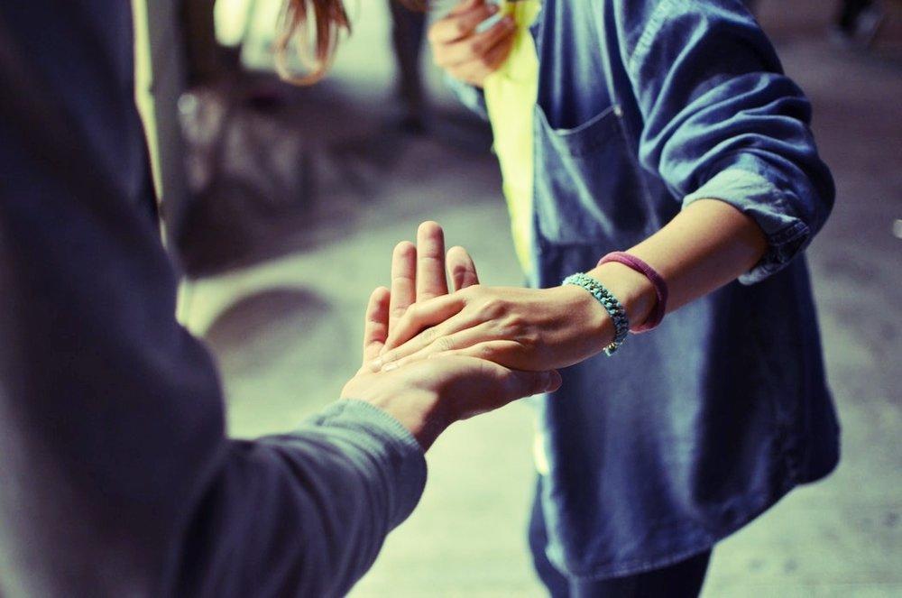Man ser to menneskers skuldre, arme og hænder. Resten er ude af fokus. Den ene (en kvinde) lægger sin hånd i den anden persons hånd, som om hun søger støtte til at holde balancen.