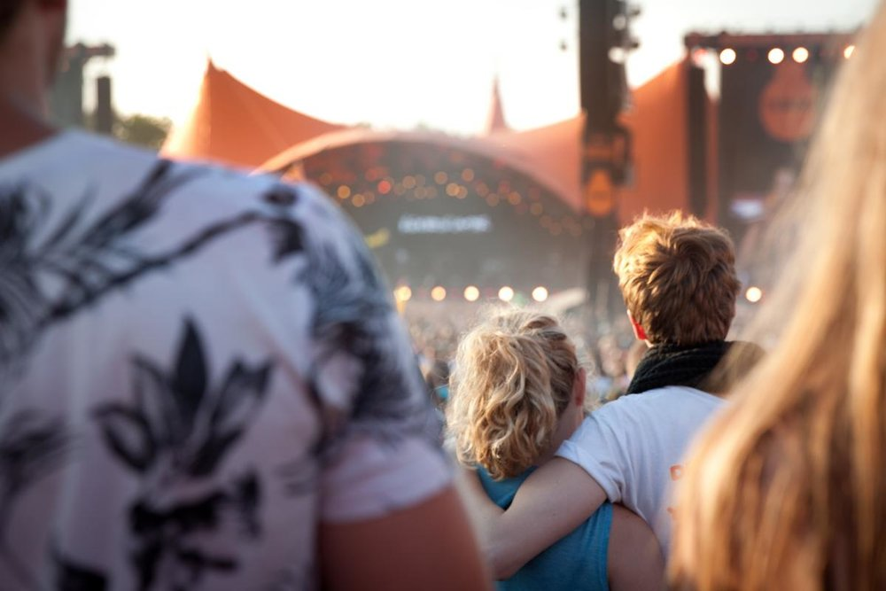 En kvinde og en mand står i menneskemængden foran Orange Scene på Roskilde Festival. De to har armene om hinandens rygge. Der er lyst som på en tidlig sommeraften.