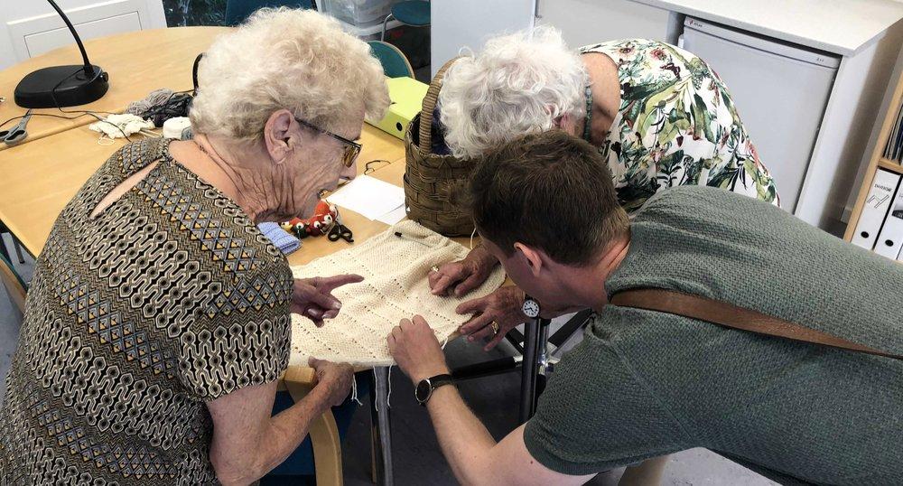 To ældre kvinder viser deres strikketøj frem.