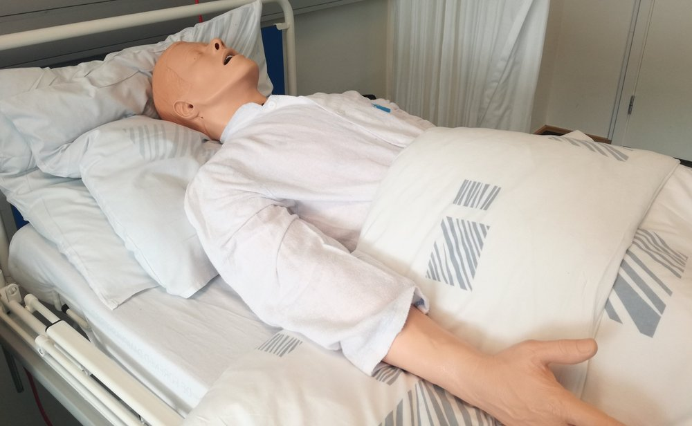En simulationsdukke ligger i en hospistalsseng.