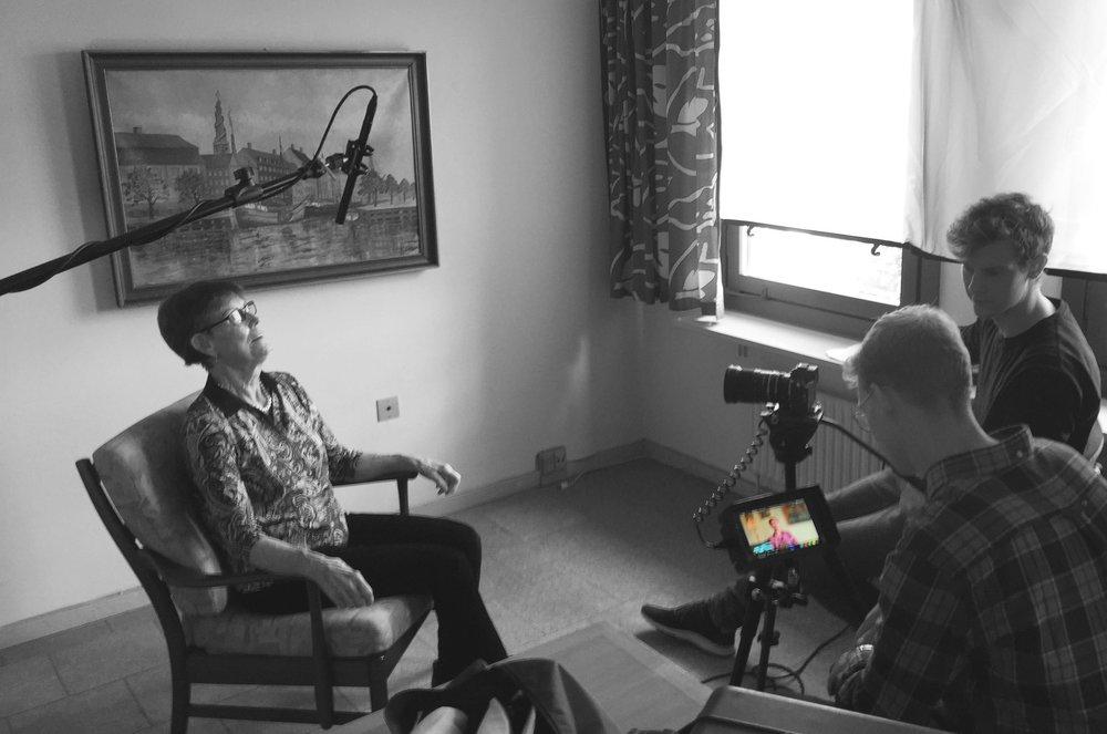 En borger bliver interviewet i sin egen stue. Hun sidder sammen med to produktionsfolk.